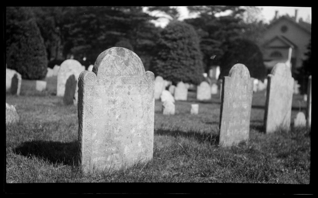 Black and white photo. A grave stone in a graveyard