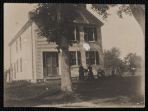 Four people, two sitting and two standing, in front of the Elbridge G. Winsor house