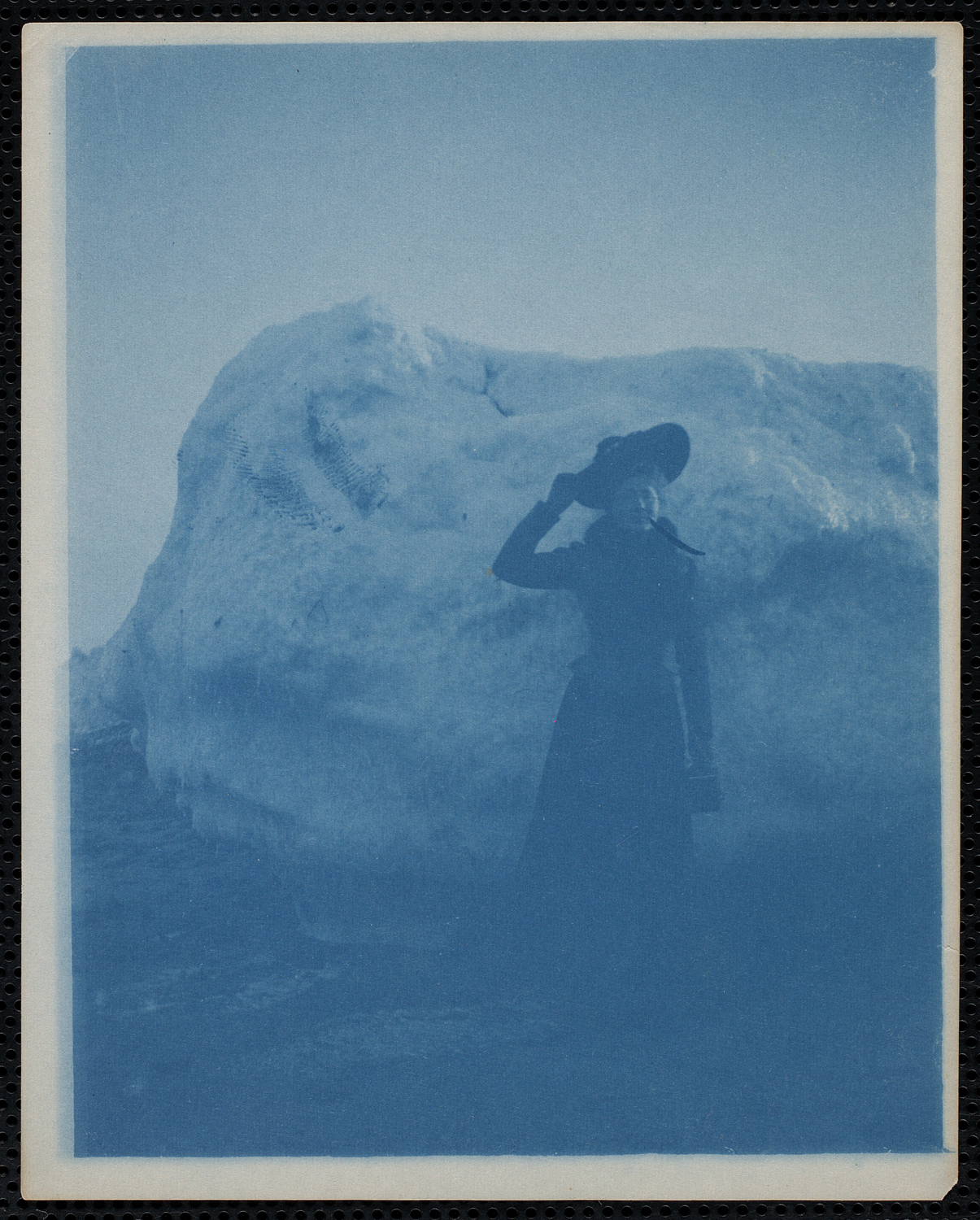 Woman standing in front of a large snow drift, undated