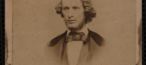 Black and white photo. Photo of the bust of a man with curly hair and a beard