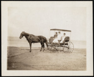 A man and two women in a horse-drawn carriage on the beach