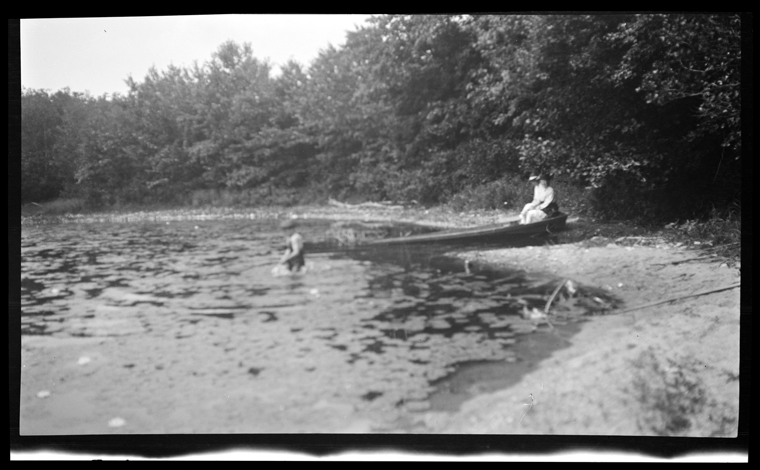 Boy in water and two people sitting in canoe on shore of Indian Pond