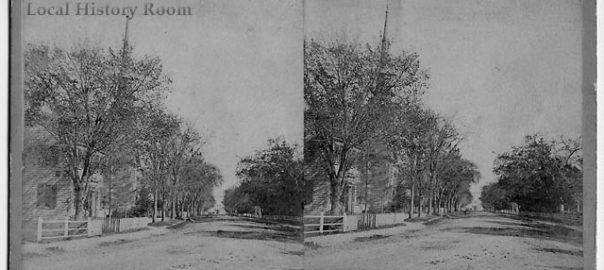 Black and white photo of a dirt road with trees. A house and a church are on the left side of the road