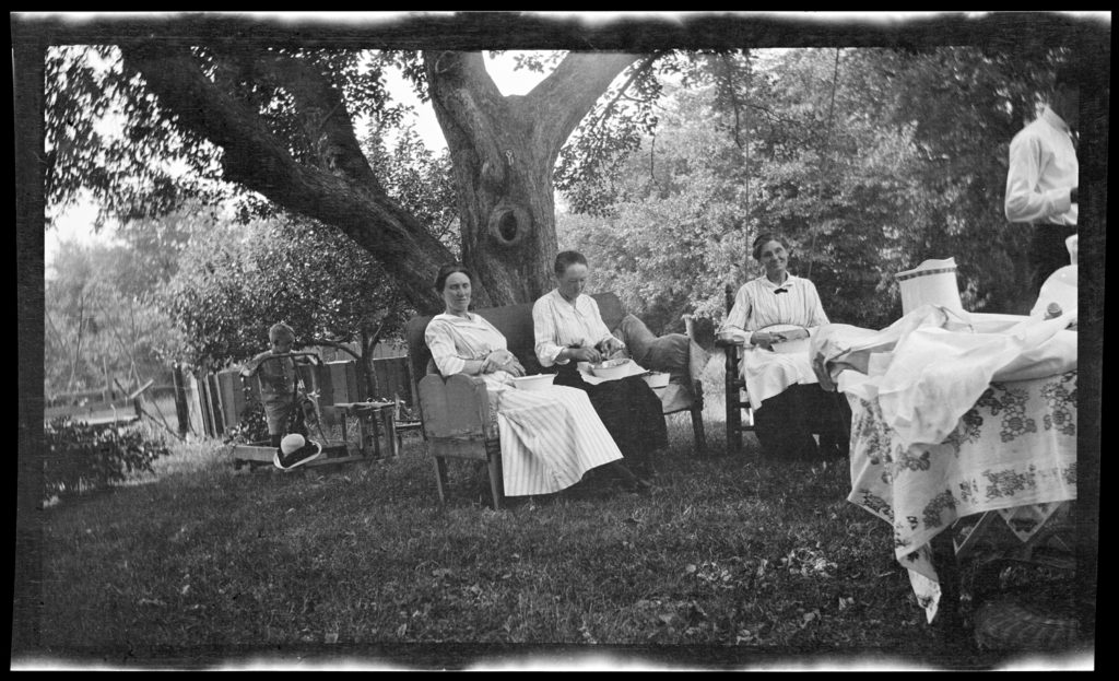 Three older women sit in chairs outside under a tree. A child plays at left; a man walks out of the frame at right.