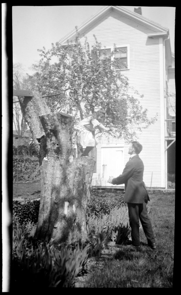 Norma Drew poised to jump from a tree stump to her father Clarence Drew