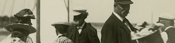 Cropped image of people on a shoreline, circa 1900