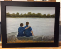 Two boys sitting by a lake with one's arm around the other