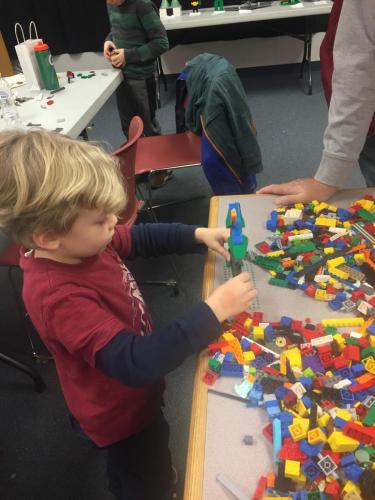 Small child building with LEGOS