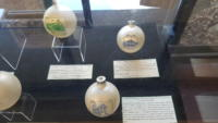 White Christmas bulbs with drawings of buildings on them