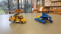 A yellow LEGO armored car and a blue LEGO hovercraft