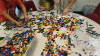 Kids building with a table full of LEGOS