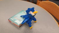 A blue LEGO bird sitting on a book