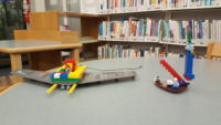 A LEGO flying wing, and a LEGO ship with a set of red stairs