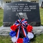 Red, white and blue wreath laid on the veterans' memorial stone